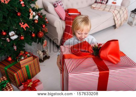 A boy with a big Christmas present near Christmas tree