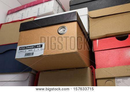 Shoe box in the closet on the shelf. One of the boxes contains information about the style, color and size shoes.