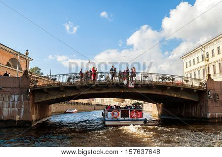 ST PETERSBURG RUSSIA-OCTOBER 3 2016. Theater bridge at the intersection of Griboyedov Canal and the Moika River in St Petersburg Russia. City landscape on St Petersburg center with walking people