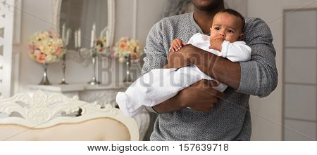 Happy African American Father Holding Smiling Baby Boy.