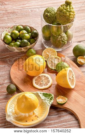 Lime and lemon with squeezer on wooden plank