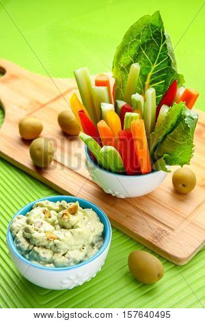 Celery and carrot sticks in the glass, olive and yogurt dip