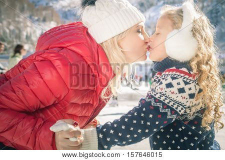 Happy mother and daughter kissing outdoor, ice skating at ice rink. Mother and daughter has winter activities. Mom, kids. Medeo stadium. Almaty.