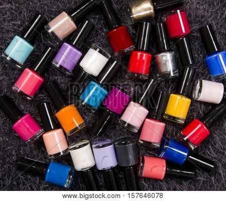 Stack of colorful bottles of nail polish. A lot of bottles of nail polish lying down on gray fur  background.