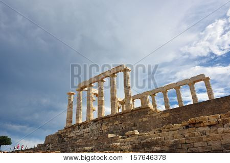 SounionGreece - Sept 21 2016: Tourists visits the Cape Sounion - Ruins of an ancient Greek temple of Poseidon before sunset under dramatic cloudy sky