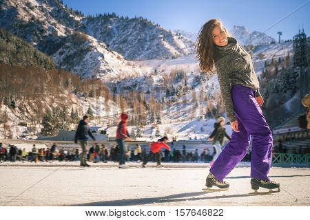 Latin girl ice skating outdoor at ice rink. Healthy lifestyle and winter sport concept at sports stadium. Ice-skating