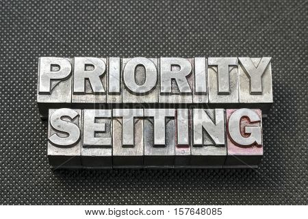 priority setting phrase made from metallic letterpress blocks on black perforated surface poster