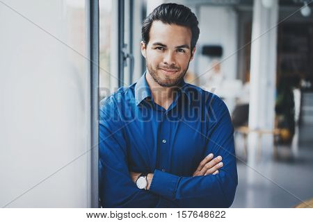 Portrait of successful confident hispanic businessman smiling and standing close from the window in modern office.Horizontal, blurred background