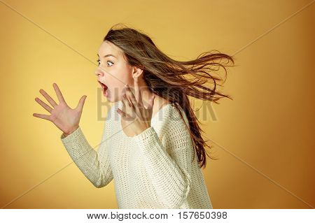 Portrait of young woman with shocked facial expression over orange studio background