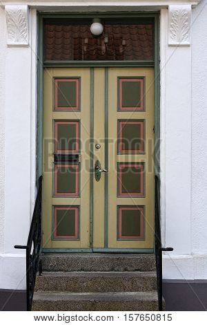 Closeup on double door in a white house
