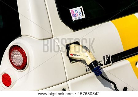 La rochelle France - April 19 2016: Electric Car Being Charged. Charging an electric car with the power supply plugged in.