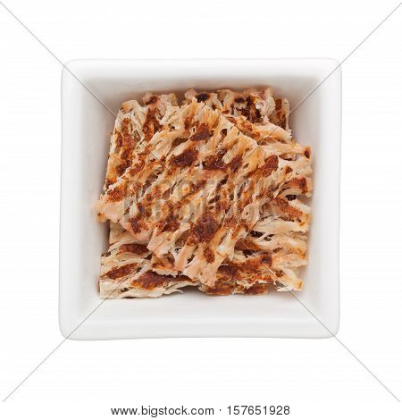 Pieces of grilled dried squid snack in a square bowl isolated on white background