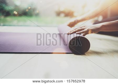 Close up view of female hands preparing mats for practice class.Young girl practicing yoga indoor.Calmness and relax, woman happiness concept.Horizontal, flares, blurred background