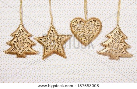 Gold metal Christmas ornaments. Star heart and Christmas tree hanging white with gold stars background.