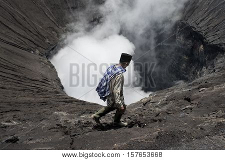 Tenggerese man walking on the edge of an active volcano in Bromo Tengger Semeru National Park. January 17 2014 - Java Indonesia