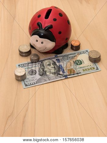 A ladybug piggy bank surrounded by coins and hundred dollar bill
