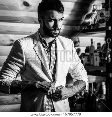 Black-white portrait of young handsome man in white suit near home bar.