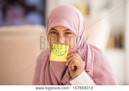 Muslim woman with fake emotion on paper smiley