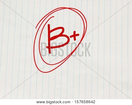 B plus (B+) grade written in red on notebook paper