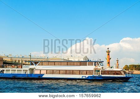ST PETERSBURGRUSSIA-OCTOBER 3 2016.Touristic sailboat floating on Neva river and St Petersburg landmarks of Vasilievsky island-rostral columns and old stock exchange building in St Petersburg Russia