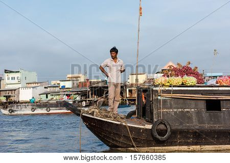 CAN THO, VIETNAM - FEB. 4: Vietnamese man selling produce at the Floating Market in Can Tho, Vietnam on February 4, 2016. Cai Rang Floating Market is the biggest floating market in the Mekong Delta.