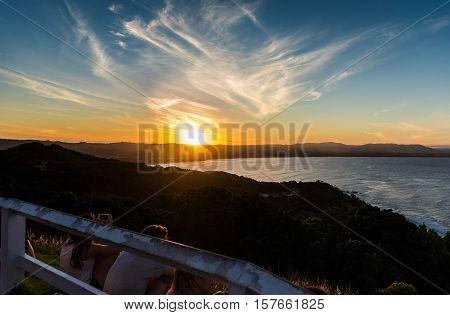 Boys & girls watching the sunset in Byron Bay, Australia