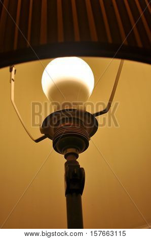 Illuminated bulb in an old lampshade. Lamp.