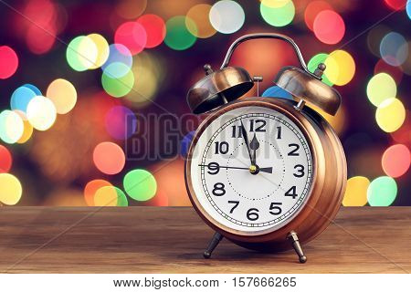 Bronze retro alarm clock at twelve o'clock on blurred Christmas background with bokeh. Midnight midday. Minutes about New year.