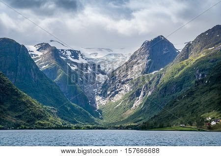 The Briksdal glacier and rocks view from the fjord water. Popular touristic attraction, Briksdalsbreen, Norway.