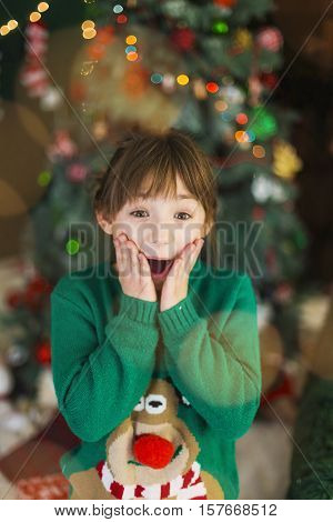 Portrait of a young surprized kid girl smiling before christmas tree background