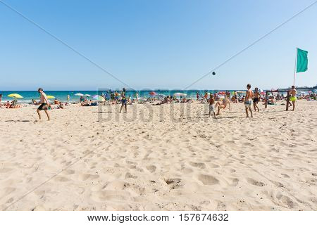 Alicante, Spain - September 9, 2016;  Beach-goers enjoyng hot summer day at Postiguet Beach Alicante Spain street and building scene