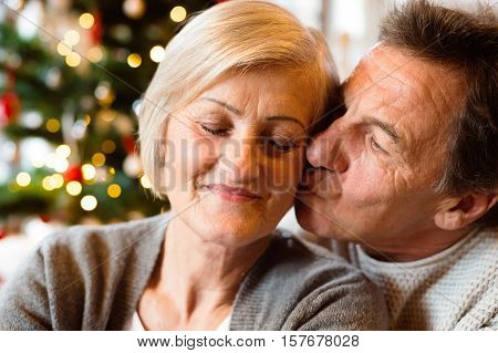 Senior couple sitting on the floor in front of illuminated Christmas tree inside their house, man kissing woman. Close up.