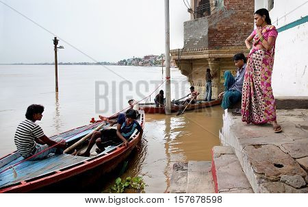Varanasi India - Jule 30 2011: Stranded Hindu pilgrims wait for flood waters of river Ganges to subside after monsoon storm.