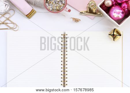 Over head flat lay view of a chic pink, gold and white Christmas desk top, Pink ornaments, office supplies and a blank open notebook