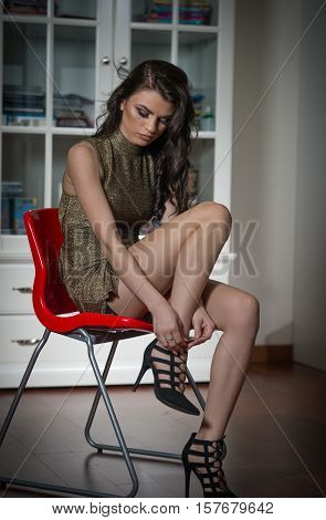 Beautiful woman showing her legs putting on or taking off high heels black shoes. Sensual attractive young girl wearing short tight fit golden fabric dress sitting on chair