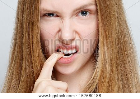 Portrait of nervous pretty young woman biting her nails. Isolated on white background. studio photo on a gray background. emotions concept. girl in the camera. portrait