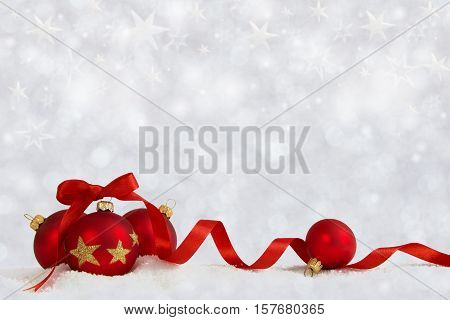 Four Christmas balls with red ribbon on artificial snow flakes. Defocused background with stars..