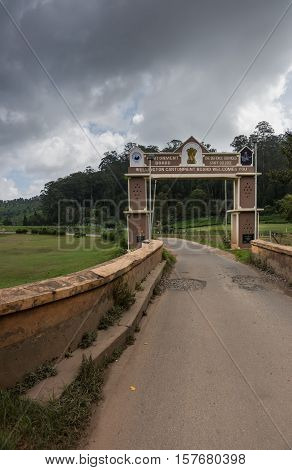 Ooty India - October 25 2013: Small rectangular side gate over narrow road into Wellington Cantonment. Features names and logos of garrison and college. Stormy sky green foliage of forest in back. Hill and meadows.