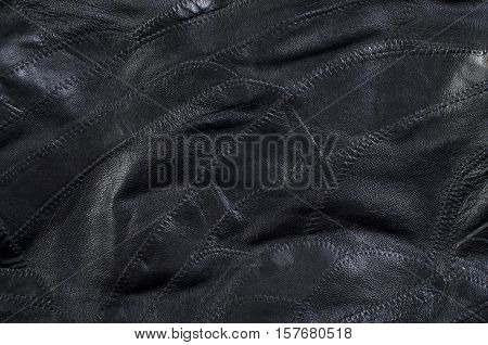 Background Black leather sewn from small pieces