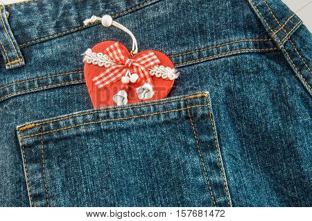 Jeans with handmade wooden red Christmas heart with ribbon and bells in pocket.