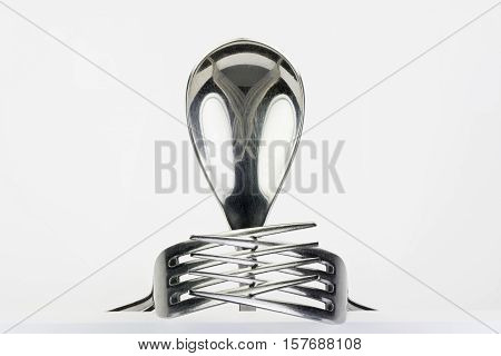 Spoon and two forks formed into conceptual figure