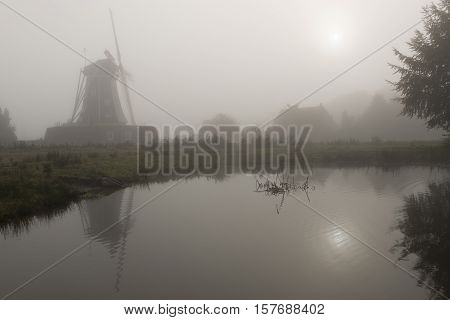 Historic corn mill called The Bataaf in Winterswijk in the early morning fog with an emerging Sun that reflectes in the nearby pond