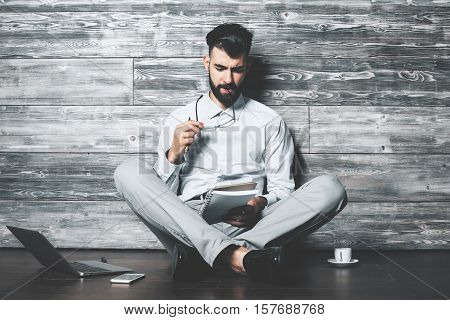 Attractive european male with notepad sitting on wooden floor with laptop smartphone and coffee cup. Young author