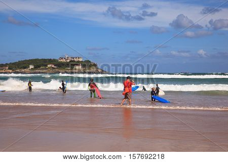 SANTANDER SPAIN - AUGUST 20: Surfers into the sea with surf boards on August 20 2016