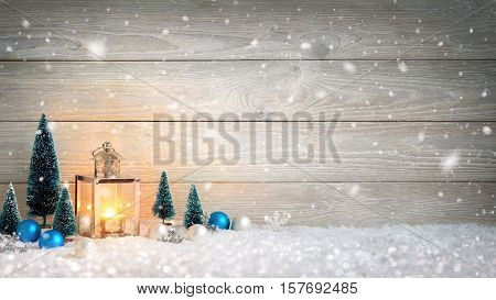 Christmas background with wooden board falling snow a burning candle in a lantern and ornaments