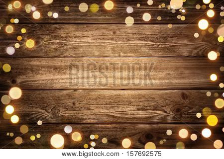 Festive rustic wood background with dark vignette and framed by glowing bokeh lights ideal for Christmas advertisement or party