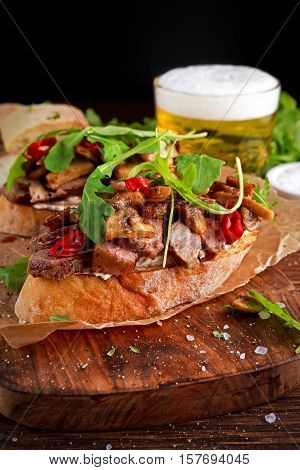 Grilled Steak Sandwich with mushrooms, goat's cheese butter and rucola leaves on top. gold beer