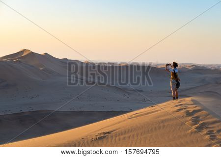Tourist Holding Smart Phone And Taking Photo At Scenic Sand Dunes Illuminated By Sunset Light In The