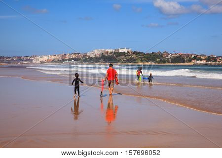 SANTANDER SPAIN - AUGUST 20: Father and son carrying their surfboard on the beach on August 20 2016