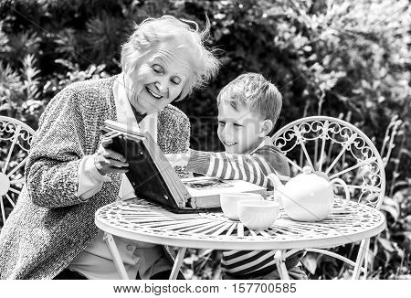 Positive grandmother and grandson spent time together in summer solar garden. Black-white photo.